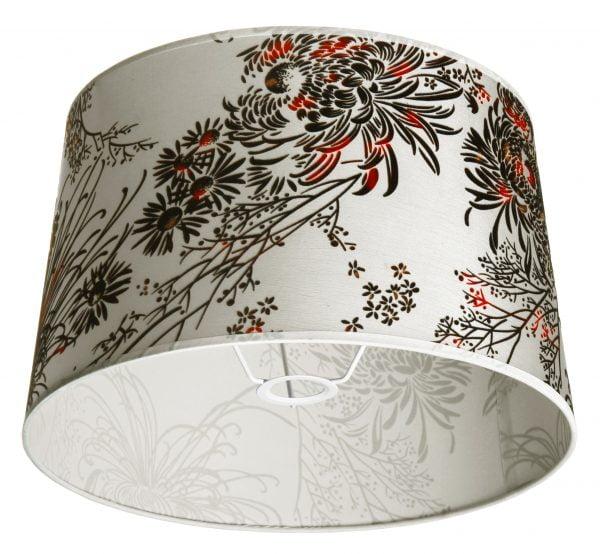 Pohjaväriltään valkoinen muuten kukkakuvioitu lampunvarjostin. Varjostin levenee ylhäältä alaspäin. Kiinnitysosa on valkoinen.