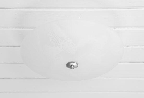 Valkoiseen, vaakalaudoitettuun kattoon asennettu pyöreä kattoplafondi. Valaisimessa on kauttaaltaan hentoja, valkoisia sulkakuvioita. Valaisin on valkoinen. Valaisimen keskellä on pyöreä, harjatun teräksen värinen levy, jonka keskellä on nuppi.