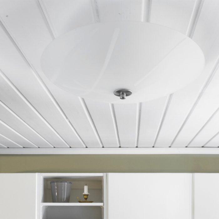 Valkoinen, lasi plafondi valkoisessa puukatossa. Tilassa on valkoiset kaapit ja oliivinvihreät seinät. Hyllyssä on kodin tavaraa.