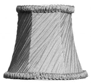 Valkoisella taustalla valokuva lampunvarjostimesta, joka levenee kevyessä kaaressa ylhäältä alaspäin. Varjostimen ylä- ja alareunat ovat kaarella. Varjostimen vasen laita on varjoisampi, kuin sen keskiosa, joka valoisin kohta. Valo korostaa varjostimen rungon luomaa kulmikkuutta. Varjostimen pohjaväri on harmaa, ja sen kangas on vinotetusti rypytetty, joka tuo kankaasta esiin eri sävyjä. Varjostimen ylä- ja alareunassa on pystysuuntaisesti rypytetty, harmaa koristenauha. Varjostin on kuvattu suoraan edestä.