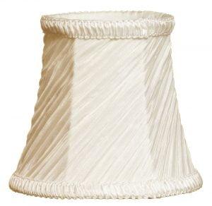 Valkoisella taustalla valokuva lampunvarjostimesta, joka levenee kevyessä kaaressa ylhäältä alaspäin. Varjostimen ylä- ja alareunat ovat kaarella. Varjostimen vasen laita on varjoisampi, kuin sen keskiosa, joka valoisin kohta. Valo korostaa varjostimen rungon luomaa kulmikkuutta. Varjostimen pohjaväri on kermanvalkoinen, ja sen kangas on vinotetusti rypytetty, joka tuo kankaasta esiin eri sävyjä. Varjostimen ylä- ja alareunassa on pystysuuntaisesti rypytetty, kermanvalkoinen koristenauha. Varjostin on kuvattu edestä.