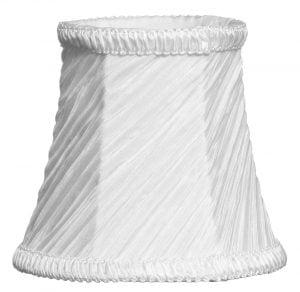 Valkoisella taustalla valokuva lampunvarjostimesta, joka levenee kevyessä kaaressa ylhäältä alaspäin. Varjostimen ylä- ja alareunat ovat kaarella. Varjostimen vasen laita on varjoisampi, kuin sen keskiosa, joka valoisin kohta. Valo korostaa varjostimen rungon luomaa kulmikkuutta. Varjostin on väriltään, ja sen kangas on vinotetusti rypytetty, joka tuo kankaasta esiin eri sävyjä. Varjostimen ylä- ja alareunassa on pystysuuntaisesti rypytetty, valkoinen koristenauha. Varjostin on kuvattu edestä.