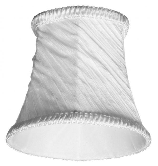 Valkoisella taustalla valokuva lampunvarjostimesta, joka levenee kevyessä kaaressa ylhäältä alaspäin. Varjostimen ylä- ja alareunat ovat kaarella. Varjostimen vasen laita on varjoisampi, kuin sen keskiosa, joka valoisin kohta. Valo korostaa varjostimen rungon luomaa kulmikkuutta. Varjostin on väriltään, ja sen kangas on vinotetusti rypytetty, joka tuo kankaasta esiin eri sävyjä. Varjostimen ylä- ja alareunassa on pystysuuntaisesti rypytetty, valkoinen koristenauha. Varjostin on kuvattu alaviistosta, jolloin sen valkoinen, aavistuksen läkuultava vuorikangas on näkyvissä.