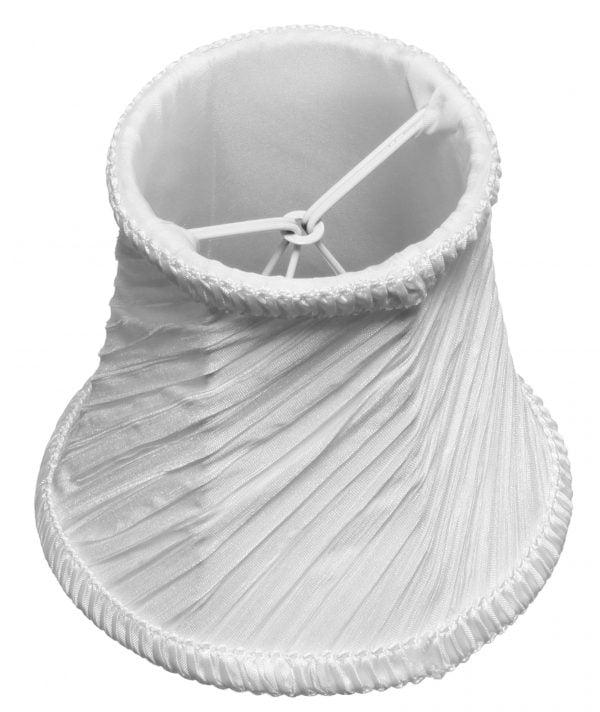 Valkoisella taustalla valokuva lampunvarjostimesta, joka levenee kevyessä kaaressa ylhäältä alaspäin. Varjostimen ylä- ja alareunat ovat kaarella. Varjostimen vasen laita on varjoisampi, kuin sen keskiosa, joka valoisin kohta. Valo korostaa varjostimen rungon luomaa kulmikkuutta. Varjostin on väriltään, ja sen kangas on vinotetusti rypytetty, joka tuo kankaasta esiin eri sävyjä. Varjostimen ylä- ja alareunassa on pystysuuntaisesti rypytetty, valkoinen koristenauha. Varjostin on kuvattu yläviistosta, jolloin yläreunasta on näkyvissä valkoinen, aavistuksen läkuultava vuorikangas sekä osa valkoisesta kiinnitystelineestä.