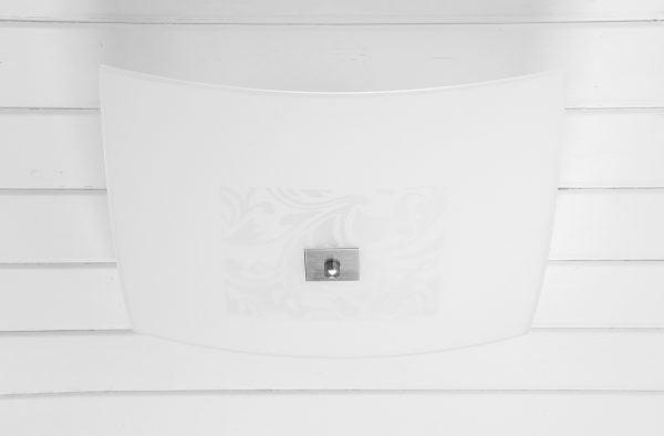 Valkoiseen, vaakalaudoitettuun kattoon asennettu kanttinen, hieman reunoilta kaareutuva kattoplafondi. Plafondin keskiosassa on vaaleanharmaa, kanttiseen muotoon tasattu ornamettikuvio. Valaisimen reunat ovat valkoiset. Kuvion keskellä on kanttinen, harjatun teräksen värinen levy, jonka keskellä on nuppi.