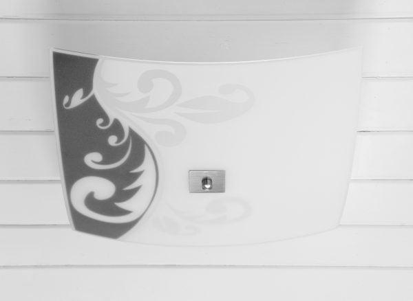 Valkoiseen, vaakalaudoitettuun kattoon asennettu kanttinen, hieman reunoilta kaareutuva kattoplafondi. Plafondin vasemmassa laidassa on matta musta/vaalean harmaa ornamentti kuviointi. Oikea laita on tasaisen valkoinen. Valaisimen keskellä on kanttinen, harjatun teräksen värinen levy, jonka keskellä on nuppi.