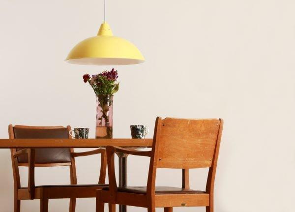 Keltainen riippuvalaisin ruskean pöydän llä, jossa on maljakossa kukkia, ja kaksi kahvikuppia. Pöydän ympärillä on 2 tuolia.