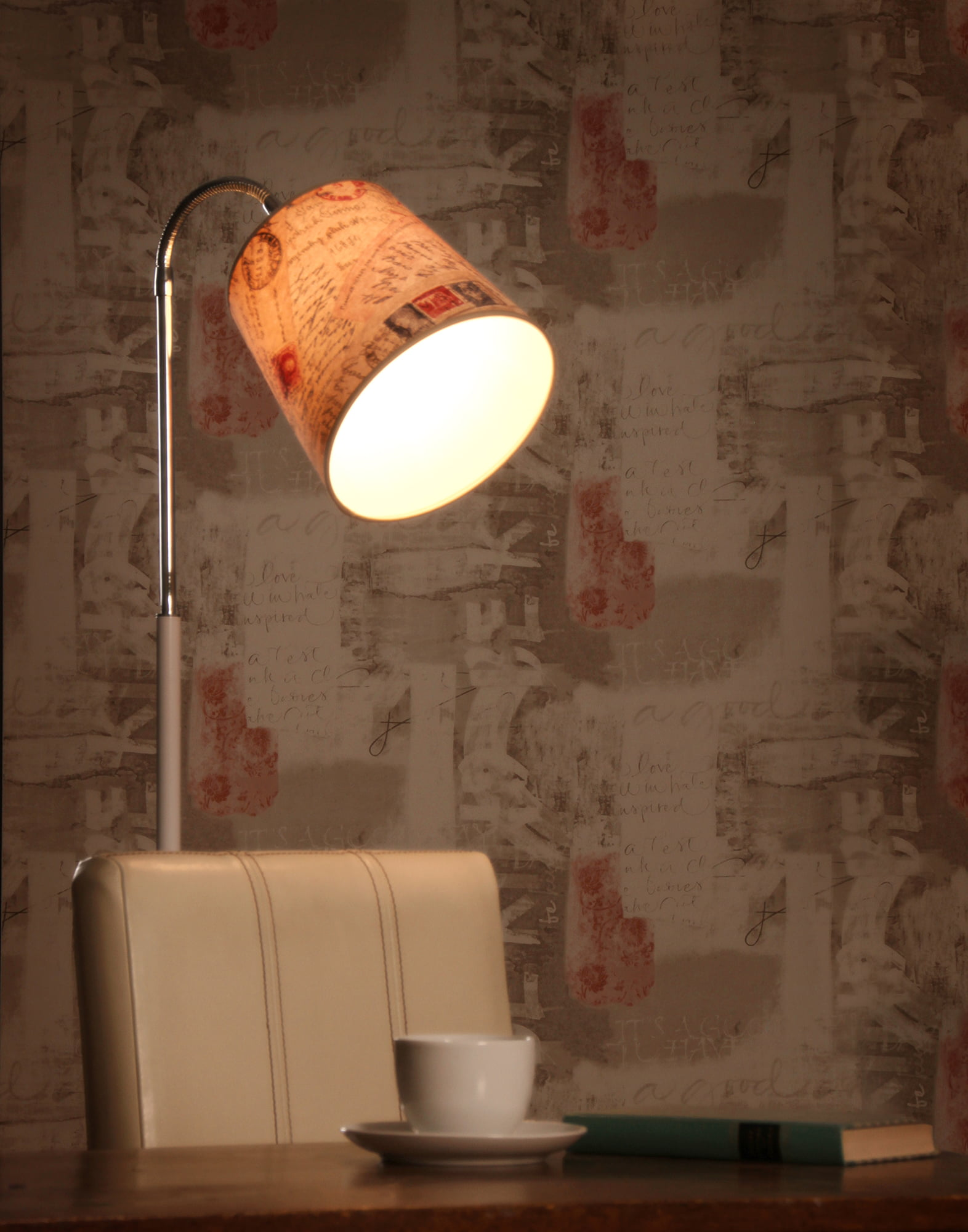 Valkoinen lattiavalaisin beigellä kippivarjostimella pöydän takana, jolla on teekupi ja kirja.