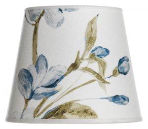 Valkoisella taustalla lampunvarjostin, joka levenee ylhäältä alaspäin. Ala ja yläreuna kaareutuvat hieman. Varjostimen taustaväri on valkoinen, ja siinä on sinisävyisiä kukkia sekä nuppuja, ja oliivinvihreitä lehtiä, jotka kurottavat vasemmalta oikealle. Varjostimen ala-ja yläreunassa on valkoinen kanttausnauha. Varjostin on kuvattu suoraan edestä.