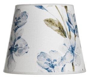 Valkoisella taustalla lampunvarjostin, joka levenee ylhäältä alaspäin. Ala ja yläreuna kaareutuvat hieman. Varjostimen taustaväri on valkoinen, ja siinä on sinisävyisiä kukkia sekä nuppuja, ja oliivinvihreitä lehtiä. Varjostimen ala-ja yläreunassa on valkoinen kanttausnauha. Varjostin on kuvattu suoraan edestä.