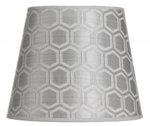 Lampunvarjostin jossa on geometrinen kuvio. Varjostin on materiaaliltaan laminoitua kangasta ja sen väri on hopea.