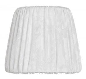 Valkoinen lampunvarjostin jossa on kukka kuvio. Varjostin on materiaaliltaan kangasta.