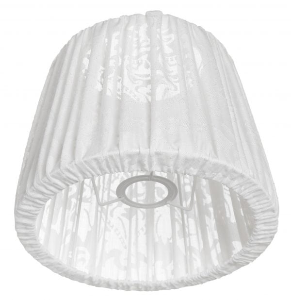Valkoisella taustalla lampunvarjostin, joka levenee suorassa linjassa ylhäältä alaspäin. Varjostimen ylä- ja alareunat ovat kaarella. Varjostimen pohjaväri on valkoinen, ja siinä on rypytetty kangas, jossa on hento ornamenttikuviointi. Varjostin on kuvattu alaviistosta, jolloin sen alareunan kankaan sisäänveto on näkyvissä. Kankaan läpinäkyvyys on myös selkeämmin esillä varjostimen alaosasa. Varjostimen valkoinen kiinnitysteline on näkyvissä.