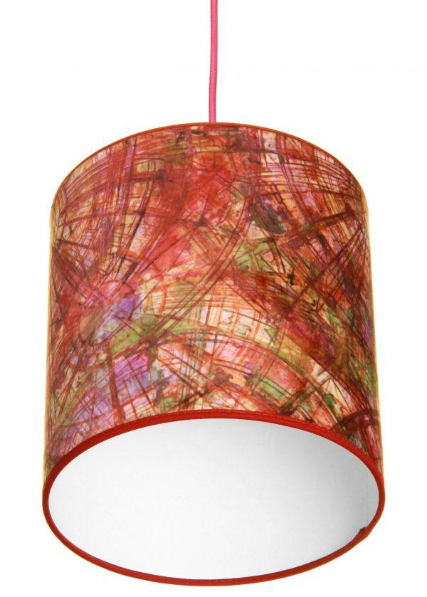 Sylinterin muotoinen kirjava lampunvarjostin. Varjostin on materiaaliltaan laminoitua kangasta. Johto on pinkki.