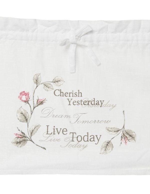 Valkoinen kangas, jossa lukee 'Cherish yesterday Dream tomorrow Live Today. Yläosassa on valkoinen nauha rusetilla.