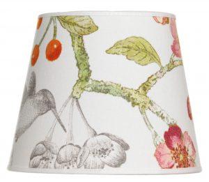 Lampunvarjostin jossa on kukka ja lintu kuvio. Varjostin on materiaaliltaan laminoitua kangasta.