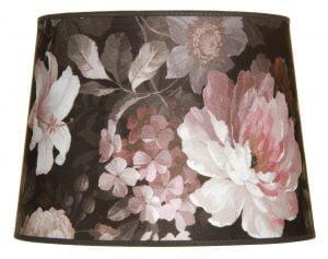 Valkoisella taustalla valokuva lampunvarjostin, joka levenee suorassa linjassa ylhäältä alaspäin. Varjostimen ylä- ja alareunat ovat kaarella. Varjostimen pohjaväri on musta, ja sitä koristavat valkoisen ja vaaleanpunaisen sävyiset kukat, sekä vihreään taittavat, harmaasävyiset lehdet. Varjostimessa on mustat kanttausnauhat ylä- ja alareunoissa. Varjostin on kuvattu suoraan edestä.