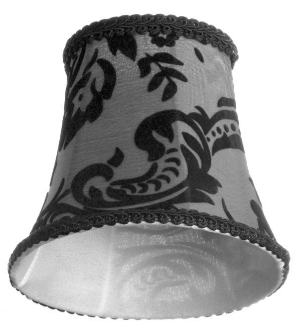 Valkoisella taustalla valokuva lampunvarjostimesta, joka levenee kevyessä kaaressa ylhäältä alaspäin. Varjostimen ylä- ja alareunat ovat kaarella. Varjostimen vasen laita on varjoisampi, kuin sen keskiosa, joka valoisin kohta. Valo korostaa varjostimen rungon luomaa kulmikkuutta. Varjostimen pohjaväri on harmaa, ja sitä koristaa musta ornamenttikuviointi. Ylä- ja alareunassa on mustat koristenauhat. Varjostin on kuvattu alaviistosta, jolloin sen valkoinen, aavistuksen läkuultava vuorikangas on näkyvissä.