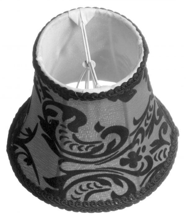 Valkoisella taustalla valokuva lampunvarjostimesta, joka levenee kevyessä kaaressa ylhäältä alaspäin. Varjostimen ylä- ja alareunat ovat kaarella. Varjostimen vasen laita on varjoisampi, kuin sen keskiosa, joka valoisin kohta. Valo korostaa varjostimen rungon luomaa kulmikkuutta. Varjostimen pohjaväri on harmaa, ja sitä koristaa musta ornamenttikuviointi. Ylä- ja alareunassa on mustat koristenauhat.Varjostin on kuvattu yläviistosta, jolloin yläreunasta on näkyvissä valkoinen, aavistuksen läkuultava vuorikangas sekä osa valkoisesta kiinnitystelineestä. Tausta on hieman näkyvissä.