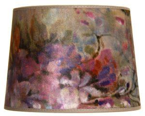 Lampunvarjostin jossa on akvarellimainen kukkakuvio. Varjostin on materiaaliltaan laminoitua kangasta.