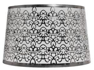 Kattolampun varjostin jonka materiaali on laminoitu kangas. Kippivarjostin on kimalteleva ja siinä on krominvärinen ornamenttikuvio.