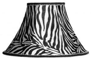 Valkoisella taustalla valokuva lampunvarjostimesta, joka levenee kevyessä kaaressa ylhäältä alaspäin. Varjostimen ylä- ja alareunat ovat kaarella. Varjostimen vasen laita on varjoisampi, kuin sen keskiosa, joka valoisin kohta. Valo korostaa varjostimen rungon luomaa kulmikkuutta. Varjostinta koristaa kauttaaltaan seeprakuviointi, jonka värit ovat musta ja hyvin vaalean hopea. Varjostimen yläreunassa on koristenauha, jonka ylälaita on musta ja alaosa on hopeinen. Alareunassa on koristenauha, jonka yläreuna on hopeinne, ja alareuna musta. Varjostin on kuvattu suoraan edestä.