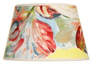 Valkoisella taustalla valokuva lampunvarjostin, joka levenee suorassa linjassa ylhäältä alaspäin. Varjostimen ylä- ja alareunat ovat kaarella. Varjostimen pohjaväri on vaalea, ja sitä koristaa vesivärimäiset kukat monissa väreissä: punaisena, keltaisena, oranssina, vaaleanpunaisena sekä sinisenä. Kuviossa on myös vihreitä lehtiä. Varjostimen ylä- ja alareunoissa on vaaleat kanttausnauhat. Varjostin on kuvattu suoraan edestä.
