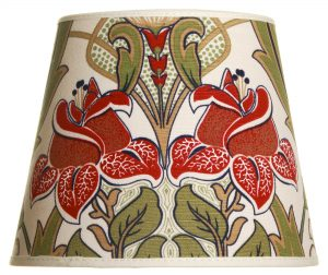 Valkoisella taustalla valokuva lampunvarjostin, joka levenee suorassa linjassa ylhäältä alaspäin. Varjostimen ylä- ja alareunat ovat kaarella. Varjostimen pohjaväri on vaalea, ja sitä koristaa kaksi graafista, punaista ruusukuviota sekä vihreät lehdet ja vaaleat kukkien varret. Kuvio on laitonjensa peilikuva. Varjostimen ylä- ja alareunassa on vaaleat kanttausnauhat. Varjositn on kuvattu edestä päin.