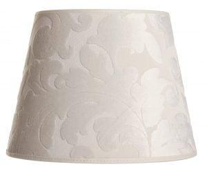 Luonnonvalkoinen lampunvarjostin, joka levenee ylhäältä alaspäin. Ylä- ja alareunat ovat kaarella. Pinnassa on koholla samettinen ornamenttikuviointi. Varjostimen ylä- ja alareunassa on kanttausnauhat.