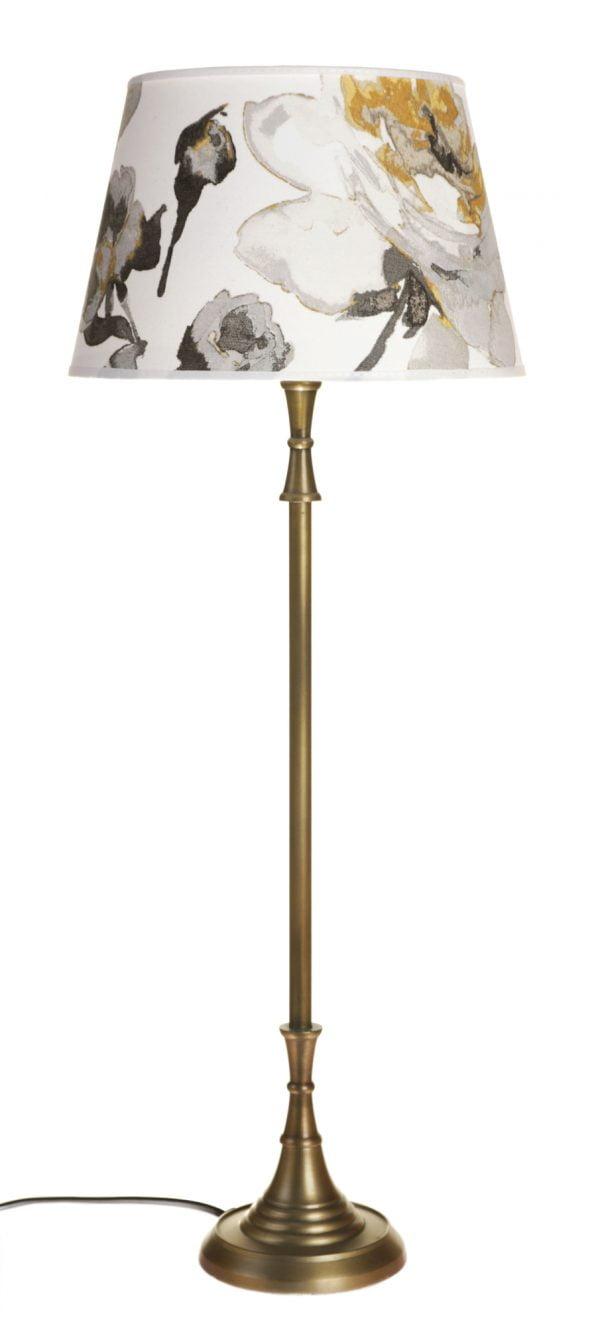 Metallinen lampunjalka jonka väri on antiikki messinki Varjostimessa on keltainen kukkakuvio.