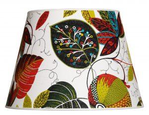 Lampunvarjostin jossa on vaalealla pohjalla värikäs lehtikuvio. Varjostin on materiaaliltaan laminoitua kangasta.