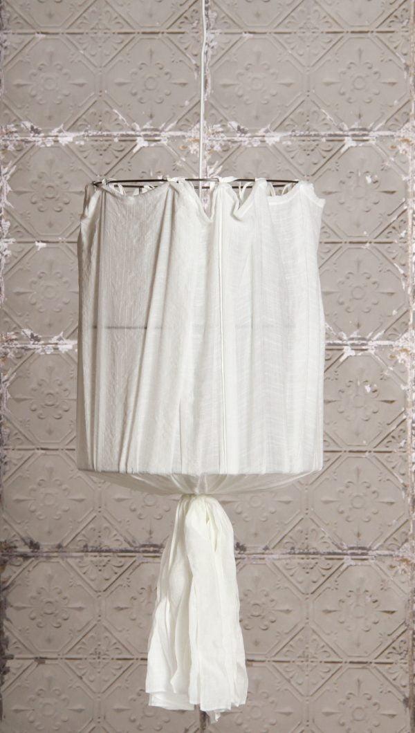 Valkoinen, pellavakankainen riippuvalaisin, jossa on nauhalla tehty rypytys yläosassa ja ruskea, kirjailtu koristekuviointi. Taustalla on vaalea, rustiikkinen laattaseinä.