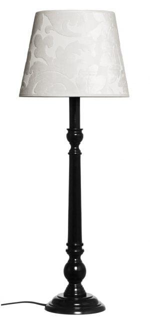 Musta lampunjalka, jossa on kiinni luonnonvalkoinen varjostin. Varjostimessa on samettinen, kohokuvioitu ornamenttikuviointi.