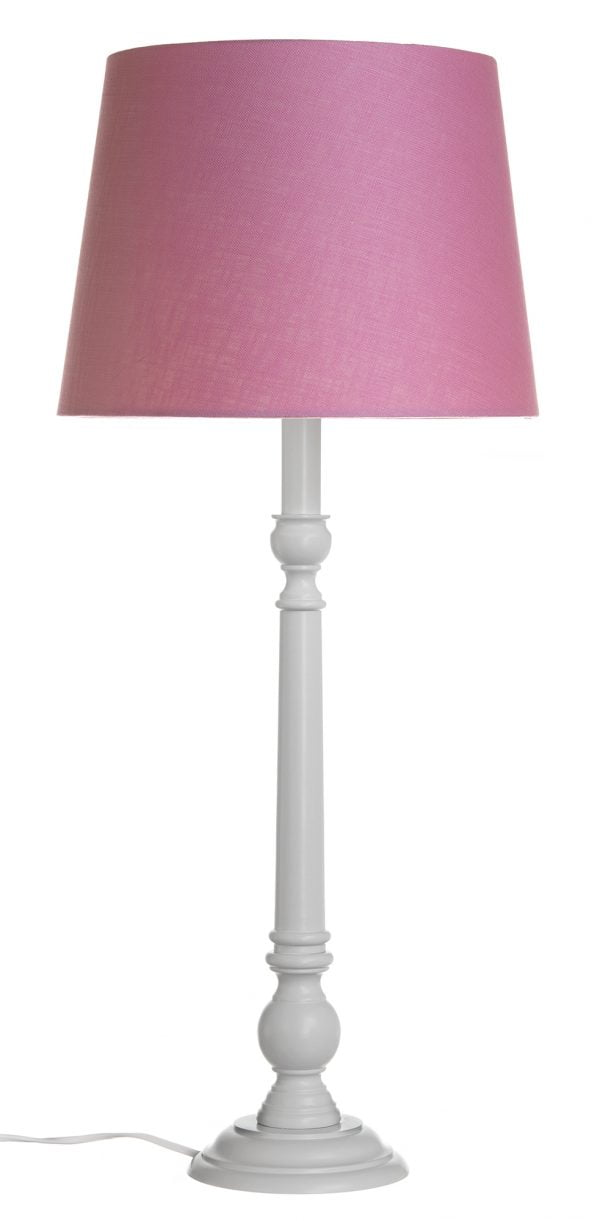 Valkoinen pöytävalaisin pinkillä, yksivärisellä varjostimella, joka levenee ylhäältä alaspäin.