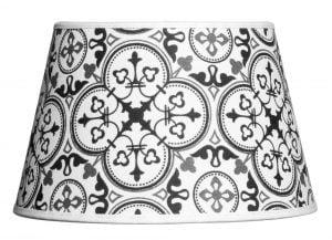 Valkoisella taustalla valokuva lampunvarjostin, joka levenee suorassa linjassa ylhäältä alaspäin. Varjostimen ylä- ja alareunat ovat kaarella. Varjostimen pohjaväri on valkoinen, ja sitä koristavat mustat ja harmaat marokkolaistyyliset kuviot. Varjostimessa on valkoiset kanttausnauhat sekä ylä- että alalaidassa. Varjostin on kuvattu edestä päin.