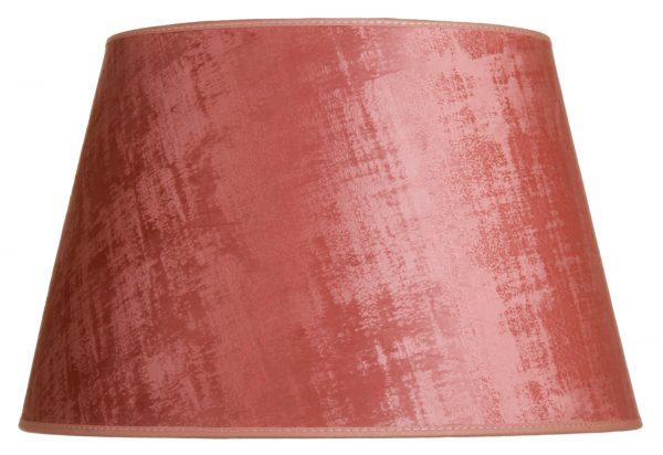 Valkoisella taustalla valokuva lampunvarjostin, joka levenee suorassa linjassa ylhäältä alaspäin. Varjostimen ylä- ja alareunat ovat kaarella. Varjostimen väri on vaaleanpunainen. Kankaan säkkikangasmainen kuviointi tulee esiin värin sävyn vaihteluissa. Varjostimen ylä- ja alareunoissa on vaaleanpunaiset kanttausnauhat. Varjostin on kuvattu edestä päin.