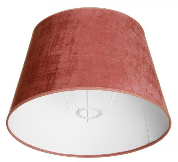 Valkoisella taustalla valokuva lampunvarjostin, joka levenee suorassa linjassa ylhäältä alaspäin. Varjostimen ylä- ja alareunat ovat kaarella. Varjostimen väri on vaaleanpunainen. Kankaan säkkikangasmainen kuviointi tulee esiin värin sävyn vaihteluissa. Varjostimen ylä- ja alareunoissa on vaaleanpunaiset kanttausnauhat. Varjostin on kuvattu alaviistosta, jolloin sen valkoinen sisäpinta sekä valkoinen kiinnitysteline ovat näkyvissä.