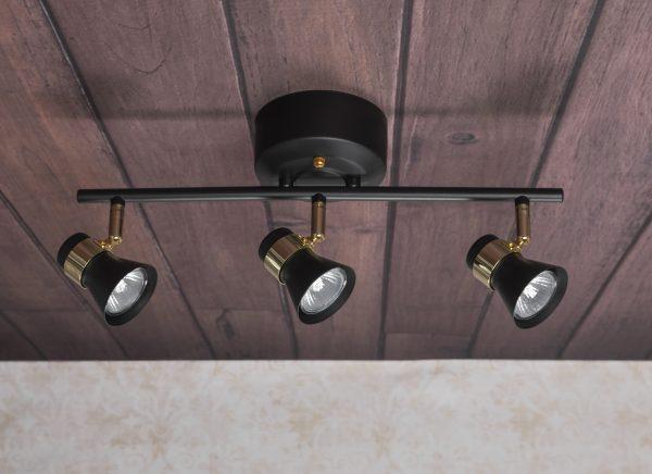 Metallinen spottivalo, värinä musta ja messinki. Kohdevalo jossa on kolme valopistettä.