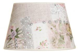 Valkoisella taustalla valokuva lampunvarjostin, joka levenee suorassa linjassa ylhäältä alaspäin. Varjostimen ylä- ja alareunat ovat kaarella tuoden esiin sen pyöreää muotoa. Varjostimen pohjaväri on vaalea, ja siinä on vaaleanpunaista, haaleaa isoa ruusukuviointia, harmaata pitsikuviointia, kuvia kristalleista sekä pieniä, vaaleanpunaisia nappeja ja kukkia, joissa on vihreitä lehtiä. Varjostimessa on vaaleanpunaiset kanttausnauhat ylä- ja alareunoissa. Varjostin on kuvattu edestä päin.