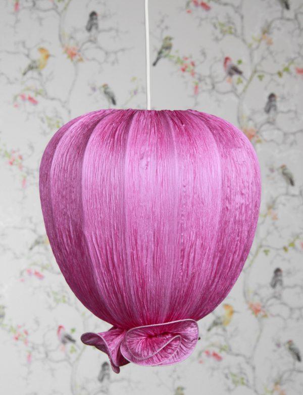 Lila kangasvalaisin, joka on valmistettu rypytetystä kreppikankaasta. Valaisin on tulppaanin muotoinen ja sen alaosassa on koristeellinen rypytys. Taustalla on vaalea tapetti kirjavin lintukuvioin.