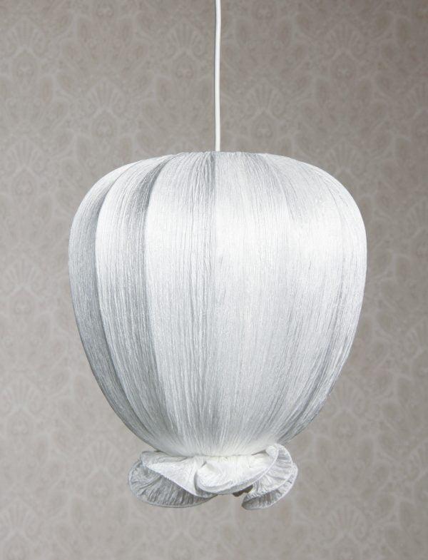 Riippuva kattovalaisin jonka materiaali on rypytetty kangas. Valaisimen väri on valkoinen.