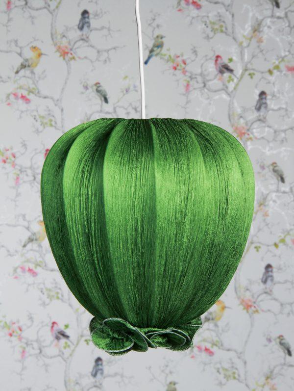 Vihreä kangasvalaisin, joka on valmistettu rypytetystä kreppikankaasta. Valaisin on tulppaanin muotoinen ja sen alaosassa on koristeellinen rypytys. Taustalla on vaalea tapetti kirjavin lintukuvioin.