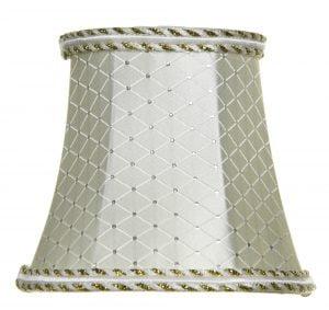 Valkoisella taustalla valokuva lampunvarjostimesta, joka levenee kevyessä kaaressa ylhäältä alaspäin. Varjostimen ylä- ja alareunat ovat kaarella. Varjostimen vasen laita on varjoisampi, kuin sen keskiosa, joka valoisin kohta. Valo korostaa varjostimen rungon luomaa kulmikkuutta. Varjostimen pohjaväri on vaalea, ja sitä koristaa valkoiset, suorat viivat, jotka muodostavat symmetrisen salmiakkikuvioinnin läpi koko kankaan. Linjojen yhtymäkohdissa on hopeiset koristeompeleet. Varjostimen ylä- ja alareunoissa on koristenuhat, joiden ylä- ja alareunoissa on kieputettuna sekä valkoista että kullanväristä nauhaa, väriviahteluiden luodessa vinoraitaisen kuvioinnin. Keskellä on valkoinen, vaakatasoinen nauha. Varjostin on kuvattu suoraan edestä.