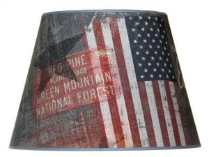 Valkoisella taustalla valokuva lampunvarjostin, joka levenee ylhäältä alaspäin. Varjostimen ylä- ja alareunat ovat kaarella tuoden esiin sen pyöreää muotoa. Varjostimen pohjaväri on sininen. Varjostimen vasemmassa reunassa ylälaidassa tumman sininen tähti, ja punaisella taustalla valkoinen teksti RED PINE PLANTED 1948 GREEN MOUNTAIN NATIONAL FOREST. Keskeltä oikeaan laitaan varjostiemssa on punavalkoinen pystyraitakuvio, ja oikeassa reunassa on tumman sinisellä pohjalla 50 tähtikuviota. . Varjostimen alalaidassa on farkkukuviointia. Varjostimen ylä- ja alareunoissa on siniset kanttausnauhat. Varjostin on kuvattu edestä päin.