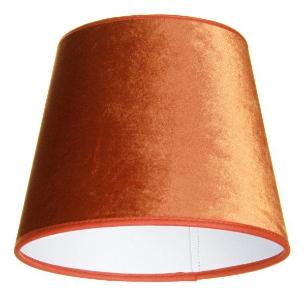 Valkoisella taustalla valokuva lampunvarjostin, joka levenee suorassa linjassa ylhäältä alaspäin. Varjostimen ylä- ja alareunat ovat kaarella tuoden esiin sen pyöreää muotoa. Varjostimen väri on terrakotta, ja sen kuosi on yksivärinen. Valon ja varjon vaihtelut tuovat sen sävyihin vaihtelua. Varjostimen ylä- ja alareunoissa on terrakotan väriset kanttausnauhat. Varjostin on kuvattu alaviistosta, jolloin sen valkoinen sisäpinta on näkyvissä.