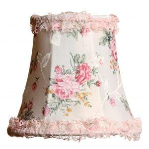 Valkoisella taustalla valokuva lampunvarjostimesta, joka levenee kevyessä kaaressa ylhäältä alaspäin. Varjostimen ylä- ja alareunat ovat kaarella. Varjostimen vasen laita on varjoisampi, kuin sen keskiosa, joka valoisin kohta. Valo korostaa varjostimen rungon luomaa kulmikkuutta. Varjostimen pohjaväri on valkoinen, ja sitä koristavat vaaleanpunaiset ruusut, pienemmän keltaiset kukat sekä vihreät kukkien varret ja lehdet. Varjostimen ylä- ja alalaidassa on vaaleanpunainen pitsinauha. Varjostin on kuvattu suoraan edestä.
