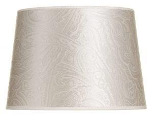 Valkoisella taustalla valokuva lampunvarjostin, joka hieman levenee suorassa linjassa ylhäältä alaspäin. Varjostimen ylä- ja alareunat ovat kaarella tuoden esiin sen pyöreää muotoa. Varjostin on väriltään vaalea, ja sitä koristaa samanvärinen paisley kuviointi. Varjostimen valo- ja varjokohdat tuovat siitä esiin eri sävyjä. Varjostimen ylä- ja alareunoissa on vaaleat kanttausnauhat. Varjostin on kuvattu edestä päin.