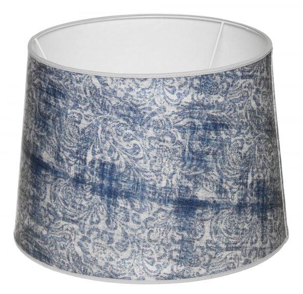 Valkoisella taustalla valokuva lampunvarjostin, joka levenee suorassa linjassa ylhäältä alaspäin. Varjostimen ylä- ja alareunat ovat kaarella tuoden esiin sen pyöreää muotoa. Varjostimen pohjaväri on valkoinen, ja sitä koristaa runsas, sininen ornamenttikuviointi. Varjostimen ylä- ja alareunoissa on valkoiset kanttausnauhat. Varjostin on kuvattu yläviistosta, jolloin sen valkoinen sisäpinta sekä osa valkoisesta kiinnitystelineestä ovat näkyvissä.