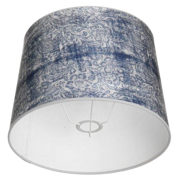 Valkoisella taustalla valokuva lampunvarjostin, joka levenee suorassa linjassa ylhäältä alaspäin. Varjostimen ylä- ja alareunat ovat kaarella tuoden esiin sen pyöreää muotoa. Varjostimen pohjaväri on valkoinen, ja sitä koristaa runsas, sininen ornamenttikuviointi. Varjostimen ylä- ja alareunoissa on valkoiset kanttausnauhat. Varjostin on kuvattu alaviistosta, jolloin sen valkoinen sisäpinta sekä valkoinen kiinnitysteline ovat näkyvissä.
