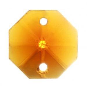 Meripihkan värinen, kahdeksankulmainen kristalli, jossa on fasettihionta. Ylä- ja alareunoissa on reiät.